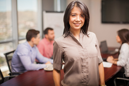 casual attire: Cute young Hispanic woman in casual attire standing in a meeting room with some of her coworkers behind