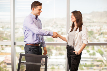 Profile view of a young handsome man giving a woman a handshake in a meeting room