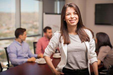 Empresaria joven vestida casualmente y sonriendo mientras sus colegas trabajan en el fondo Foto de archivo - 41611866