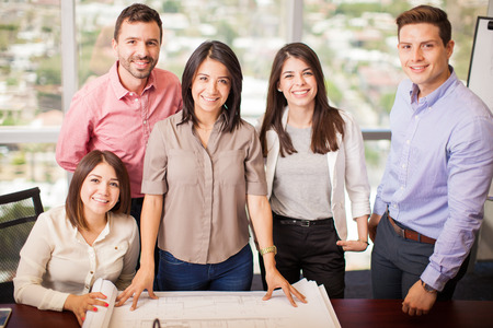 workers group: Portrait of a group of Hispanic architects working on a project in a meeting room
