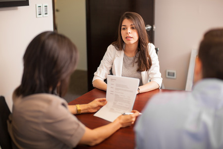 casual: Portrait of a young Hispanic woman sitting in front of two people during a job interview