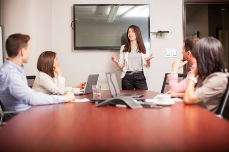 Beautiful young brunette speaking in front of her colleagues in a meeting room Stock fotó - 41612025