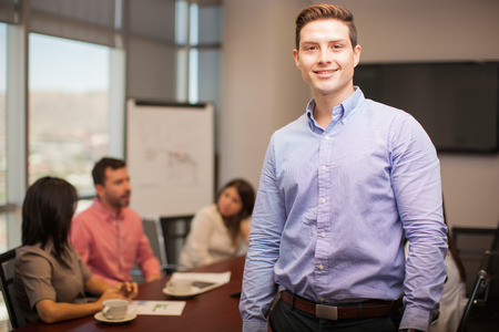 happy workers: Portrait of a young attractive man standing in a meeting room with his colleagues working in the background Stock Photo