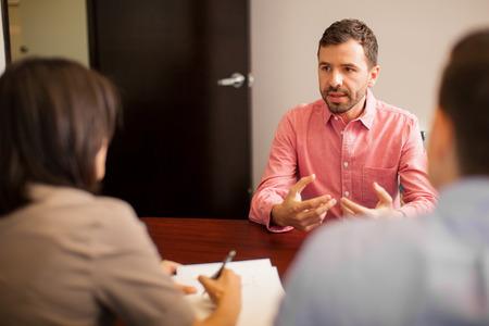 Retrato de un joven atractivo hablar de sí mismo durante una entrevista de trabajo