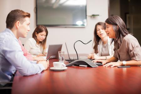 Gruppe von Menschen im Gespräch mit einem Mikrofon über einen Konferenzanruf bei der Arbeit Lizenzfreie Bilder