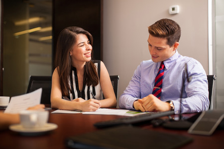 fling: Cute Hispanic businesswoman looking at one of her coworkers and flirting with him during a meeting Stock Photo