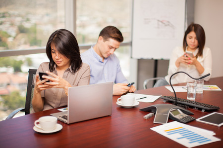 office space: Hispanic people in a meeting room ignoring their work and doing some social networking on their smartphones Stock Photo