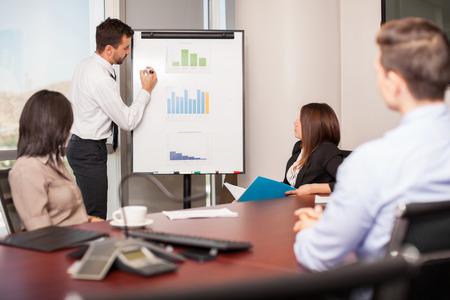ejecutivos: Hombre de negocios joven que presenta algunos resultados en un Flipboard a un grupo de personas en una sala de reuniones