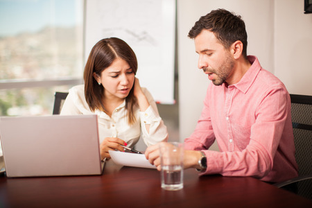 casual attire: Young man and woman in casual attire analyzing some documents while working in a meeting room