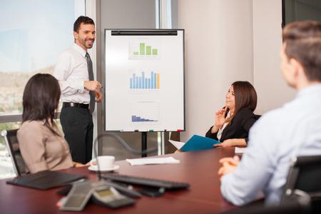 Attraktive junge Mann, der ein Verkaufsgespräch zu einer Gruppe von Kunden in einem Besprechungsraum
