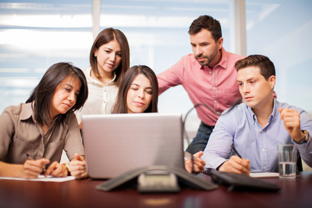casual attire: Portrait of five people in casual attire looking at a laptop while working in a conference room