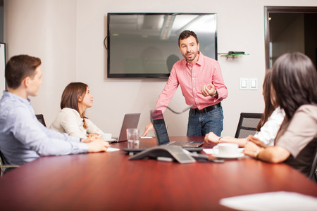 leader: Grupo de personas en una sala de escucha a un hombre que presenta algunas ideas