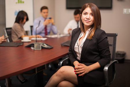 ley: Joven empresaria hisp�nica que se sienta en una sala de reuniones con algunos de sus colegas