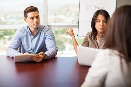 recursos humanos: Un par de trabajadores de recursos humanos de entrevistar a una mujer para un puesto de trabajo Foto de archivo