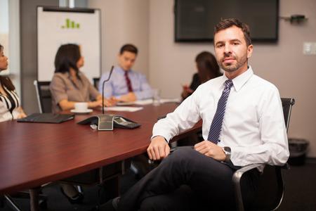 Hombre de negocios hispánico joven apuesto y confidente que se sienta en una sala de conferencias con algunos clientes Foto de archivo
