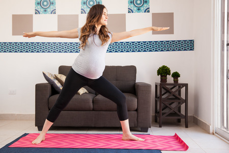 pregnancy yoga: Pretty young brunette doing some yoga exercises at home during her pregnancy