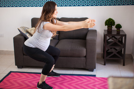 pregnant exercise: Full length view of a young pregnant mother exercising and doing squats at home