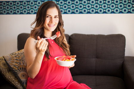 woman on couch: Goodlooking pregnant woman eating healthy food in her living room and smiling