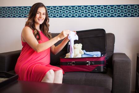 femme valise: Belle femme enceinte hispanique emballage des v�tements de b�b� pour l'h�pital Banque d'images