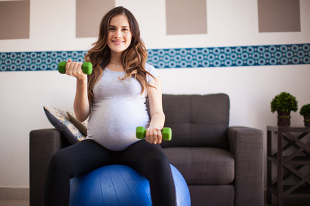 weight room: Cute Latin pregnant woman using dumbbells and a stability ball for exercising in the living room