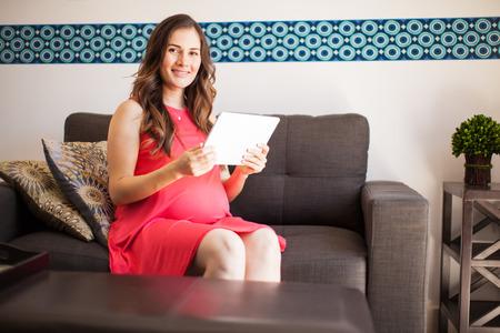 embarazada: Retrato de una atractiva mujer embarazada relajarse en el sal�n y la lectura en un equipo Tablet PC Foto de archivo