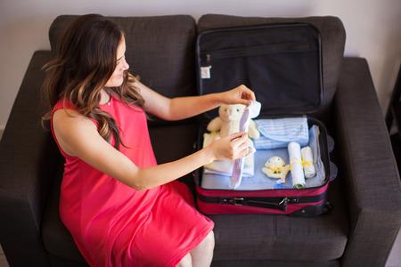 femme valise: Jeune brune enceinte emballage des v�tements pour son b�b� dans une valise avant d'aller � l'h�pital