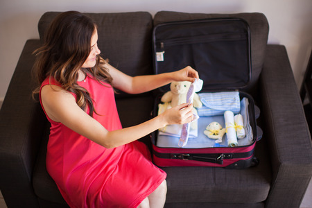 packing suitcase: Young pregnant brunette packing some clothes for her baby in a suitcase before going to the hospital
