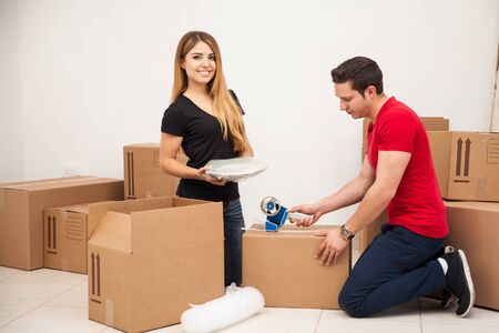 move in: Happy young woman helping her boyfriend pack his things and move in to her apartment Stock Photo