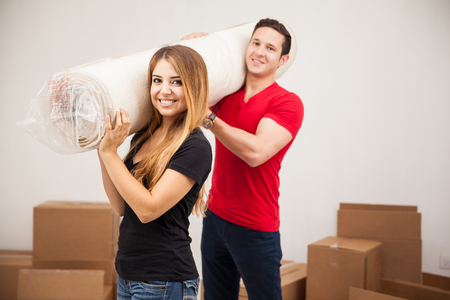 carrying: Portrait of a cute Hispanic young couple carrying a rug for their new home and smiling
