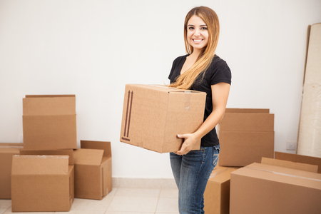 moving box: Beautiful young woman carrying some boxes and moving to her new place Stock Photo