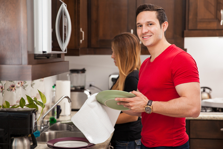 dish: Portrait of a young handsome man washing the dishes with her wife at home