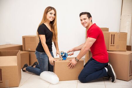 moving out: Portrait of a young Hispanic couple packing their stuff and moving out to their new apartment