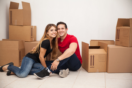 moving box: Portrait of a happy young couple sitting in the floor in a room full of boxes while moving to their new apartment