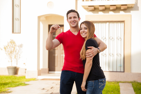 suburbs: Good looking Hispanic young couple holding the keys to a house they just bought