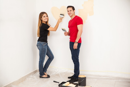 some: Beautiful young woman painting a room with her husband and having some fun painting a heart