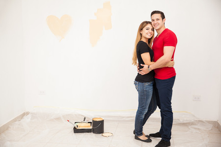 Full length portrait of a young Hispanic couple painting and decorating their new home