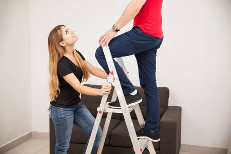holdings: Cute young woman holding a ladder while her boyfriend fixes something in the ceiling Stock Photo