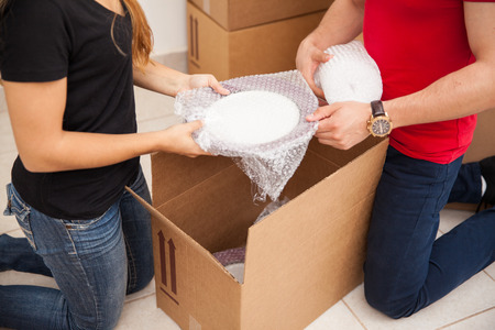 moving out: Closeup of a young couple using bubble wrap to pack their stuff in boxes before moving out