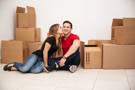 first home: Cute young couple moving into their first home and sitting in a room full of boxes