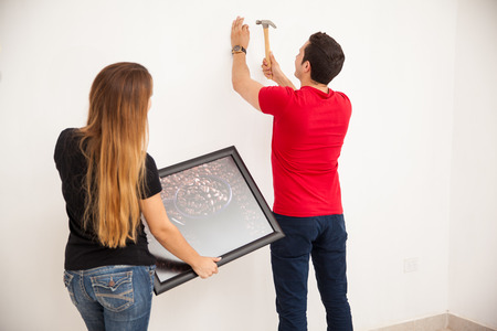 helps: Young man nailing a picture on the wall with a hammer while his wife helps