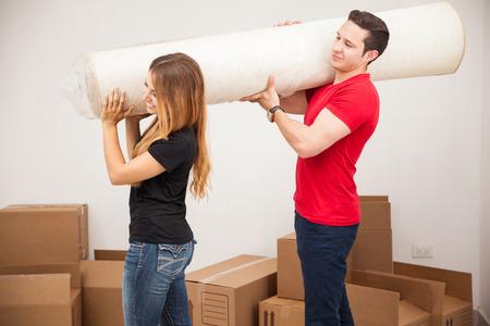 pareja de esposos: Vista de perfil de un matrimonio joven llevaba una alfombra enrollada a su nuevo apartamento