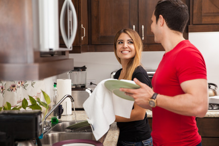 adult couple: Happy newlyweds washing the dishes together and looking at each other