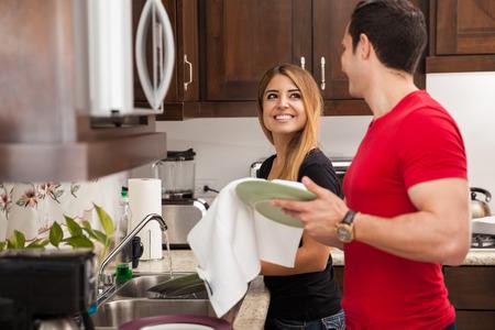 wash dishes: los recién casados ??feliz y lavado de los platos juntos y mirando el uno al otro