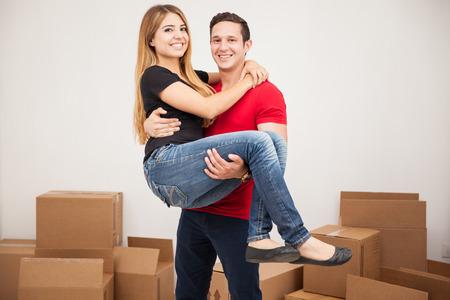 Portret van een jonge Spaanse man die haar vrouw in hun gloednieuwe huis draagt