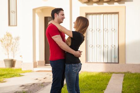 pareja en casa: Vista de perfil de una joven pareja en el amor, de pie delante de la casa que acaba de comprar