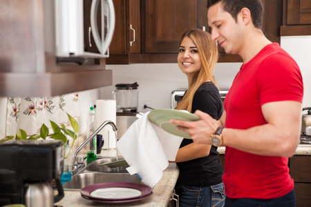 Attractive young Latin couple washing the dishes together at home Stockfoto
