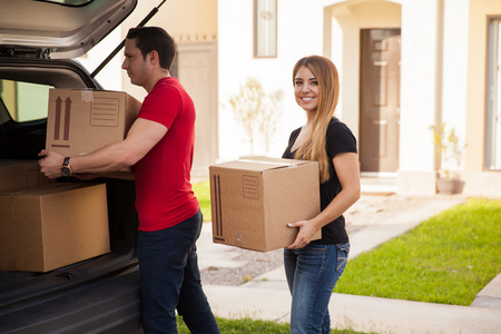 man carrying box: Cute young Hispanic couple loading their stuff in their car and moving to their new home Stock Photo