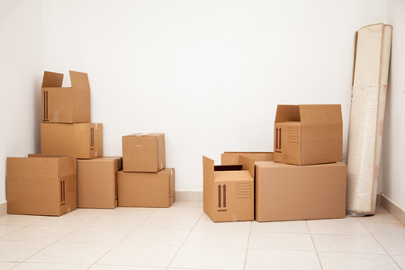 moving box: Empty room full of cardboard boxes for moving to a new home