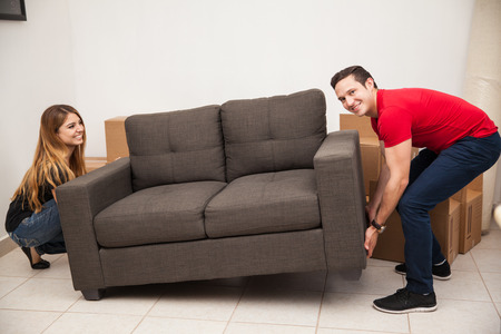 couple on couch: Young couple of newlyweds trying to move a couch to their new apartment