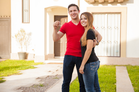 Happy young couple showing the keys to their new home and smiling Stock Photo